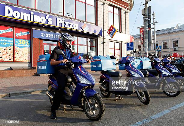 A delivery rider sits on a scooter outside a Domino's Pizza Inc store in Kiev Ukraine on Monday May 7 2012 Ukraine's central bank is unlikely to...