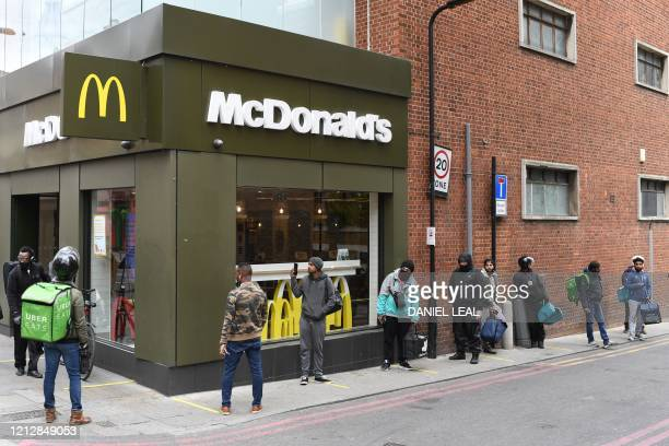 Delivery riders queue up outside a McDonald's restaurant in east London on May 13, 2020 after the restaurant opened for delivery only orders as the...