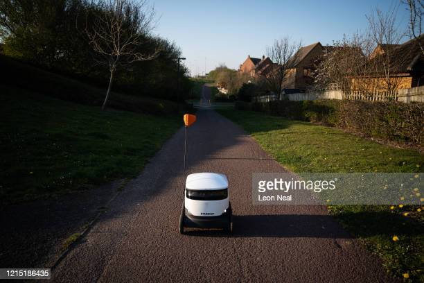Delivery robot negotiates the empty pavements and pathways as it makes a home delivery on March 27, 2020 in Milton Keynes, England. With the country...