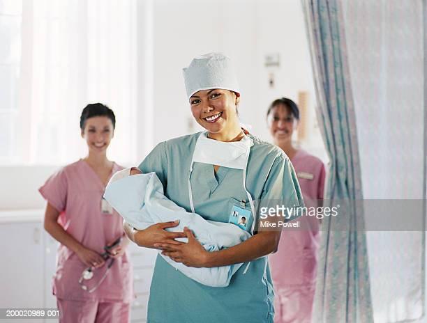 delivery room nurse holding baby, nurses in background - enfermera fotografías e imágenes de stock