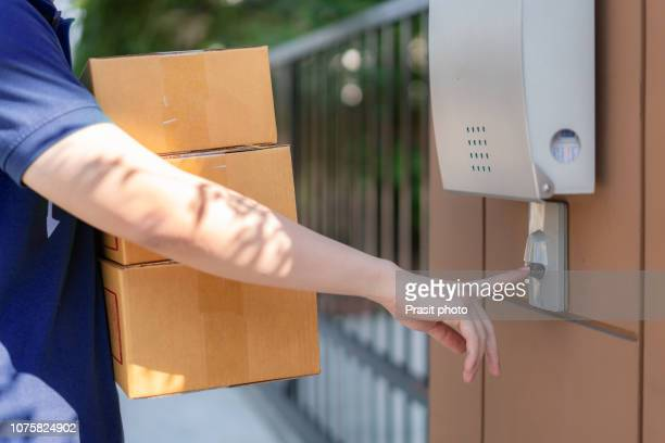 delivery service courier ringing the house doorbell with boxes in hands - ringing doorbell stock pictures, royalty-free photos & images