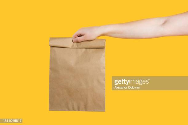 delivery service service concept. male hand holding eco craft takeout food bag on isolated yellow background studio. packaging mock up template. copy space - lunch bag stock pictures, royalty-free photos & images