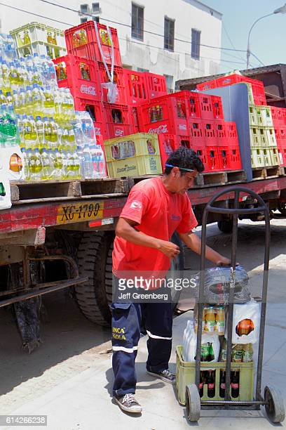 Delivery truck, deliveryman unloading soft drinks onto dolly cart, Calle 28 de Julio.