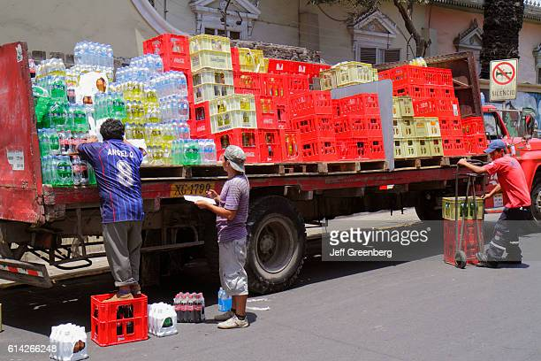 Delivery truck, deliverymen unloading soft drinks onto dolly carts, Calle 28 de Julio.