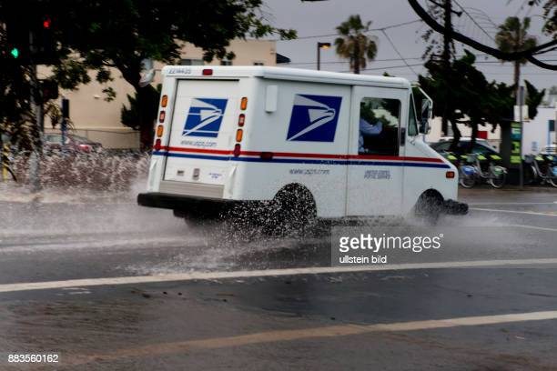A USPS delivery truck on a partly flooded street in Pacific Beach