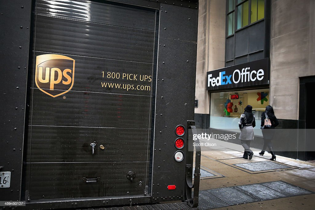 A UPS delivery truck sits in front of a FedEx Office store