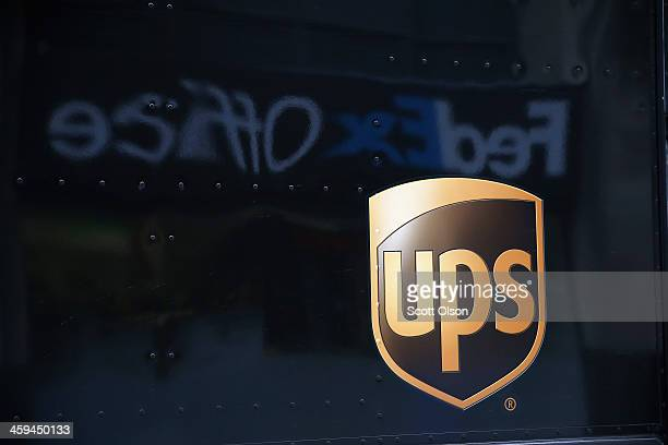 UPS delivery truck sits in front of a FedEx Office store on December 26 2013 in Chicago Illinois Bad weather and a higher than expected demand from...