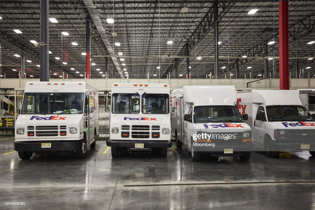 Delivery trucks sit parked at the FedEx Corp. Ground distribution center in Jersey City, New Jersey, U.S., on Tuesday, Aug. 7, 2018. FedEx is heading into fiscal 2019 running on all cylinders, with revenue growth and margin expansion expected across all three of its segments. Photographer: Marc McAndrews/Bloomberg via Getty Images