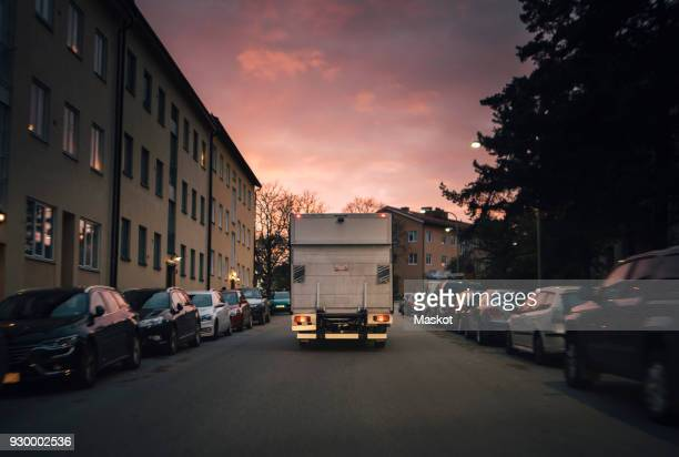 Delivery van moving on road amidst parked cars in city against sky at sunset
