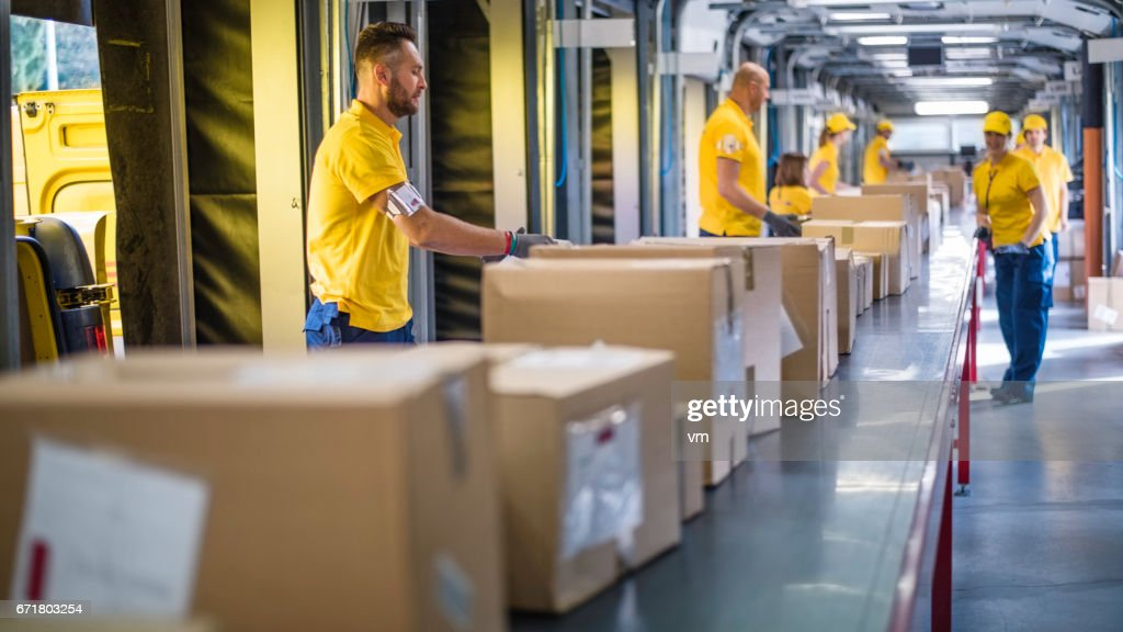 Delivery warehouse workers handling packages on conveyor belt : Stock Photo
