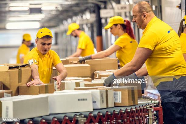 delivery warehouse workers handling packages on conveyor belt - post structure stock pictures, royalty-free photos & images