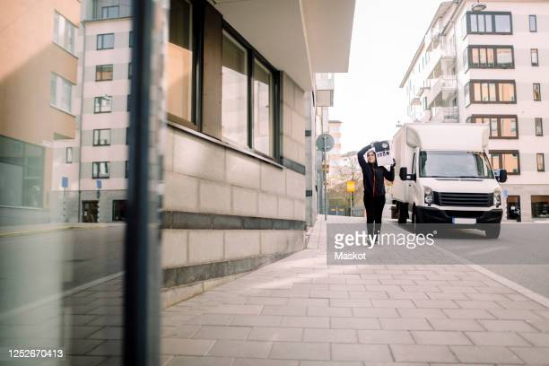 delivery woman carrying package while walking on footpath in city - focus on background stock pictures, royalty-free photos & images