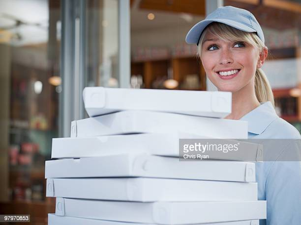 Delivery woman carrying stack of pizza boxes