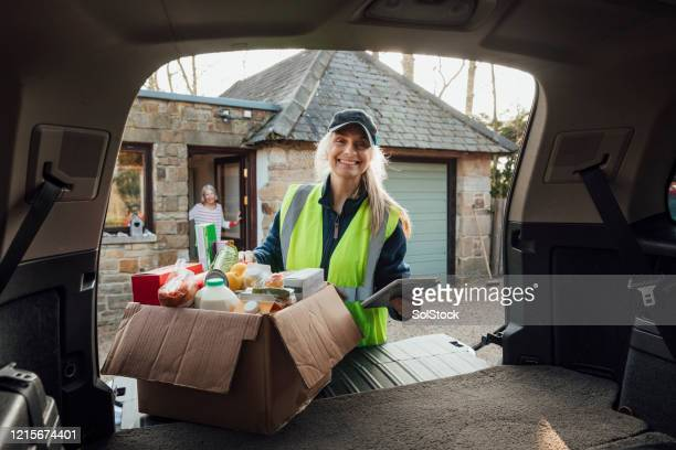 delivery woman smiling - volunteer stock pictures, royalty-free photos & images