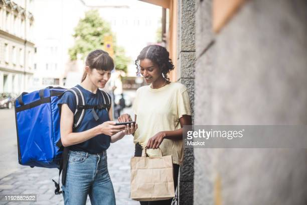 delivery woman taking sign from female customer while delivering package - consegna a domicilio foto e immagini stock