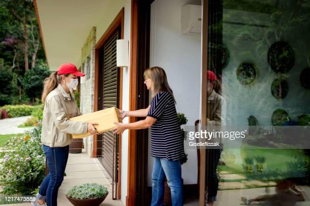 de vrouw die van de levering masker gebruikt, brengend een doos aan een woonplaats - ontvangen stockfoto's en -beelden