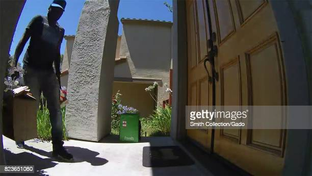 A delivery worker for the Amazon Fresh grocery delivery service his face obscured in shadow delivers a parcel of groceries to a suburban home in San...