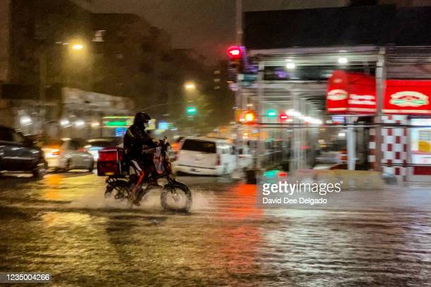 Delivery worker makes their way in the rainfall from Hurricane Ida during a flood on Intervale Avenue on September 1 in the Bronx borough of New York...