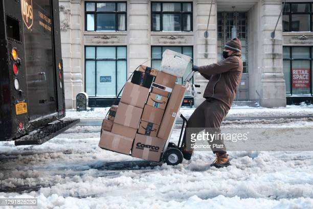 Delivery worker walks through the snow in Manhattan on December 17, 2020 in New York City. New York City received 6 to 8 inches of snow in an...