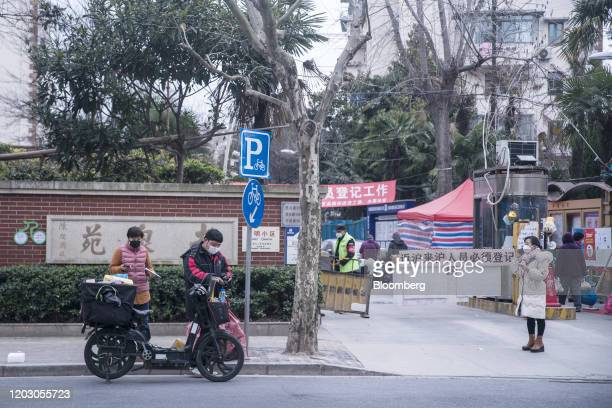 Delivery workers wearing protective masks wait for residents to collect their parcels at a makeshift checkpoint, set up to control the flow of...