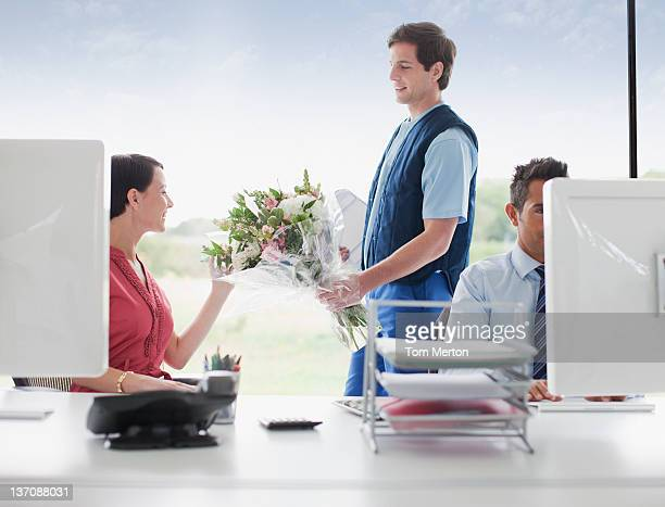 Deliveryman delivering flowers to businesswoman in office