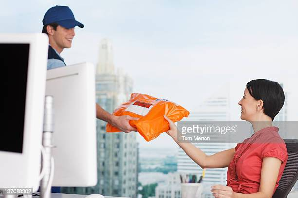 Deliveryman di consegnare il pacco da donna in carriera