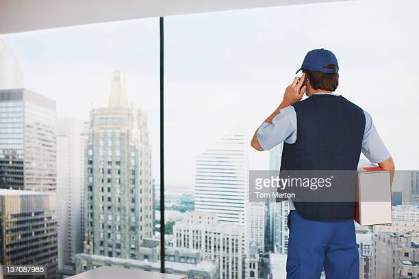 Deliveryman in office with package talking on cell phone