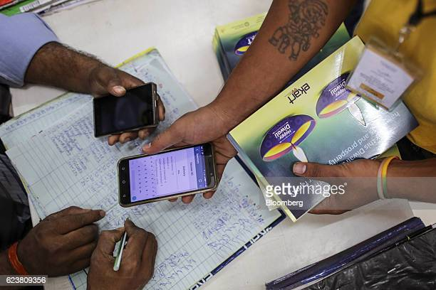 A deliveryman known as a Wishmaster for Flipkart Online Services Pvt's Ekart Logistics service shows a smartphone to a colleague at the company's...