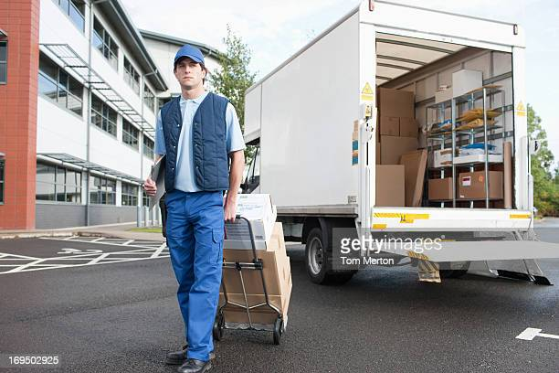 deliveryman puling boxes on hand truck - delivery person stock pictures, royalty-free photos & images