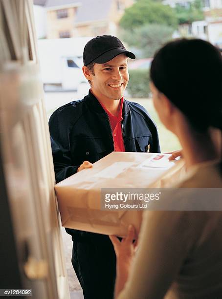 Deliveryman Standing at the Front Door of a House and Handing a Parcel to a Young Woman