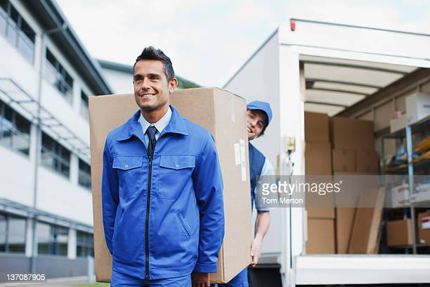 Deliverymen carrying large box from van