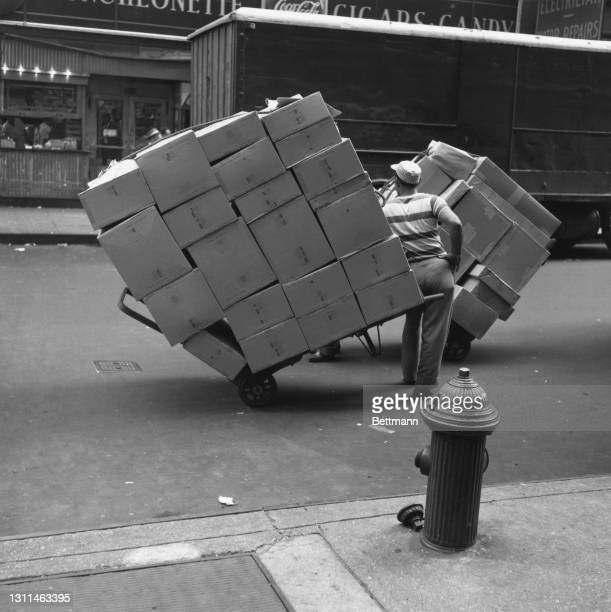 Deliverymen with sack trucks loaded with cardboard boxes pay no heed to the traffic as they stop for a chat on Eighth Avenue and 36th Street in the...