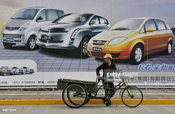 Deliverywoman pushes her tricycle past a billboard featuring vehicles manufactured by Changan Automobile Group at the venue for the 2005 Shanghai...