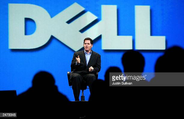 Dell CEO Michael Dell, suffering from a broken ankle, delivers a keynote address while sitting in a chair at the 2003 Oracle World Conference...