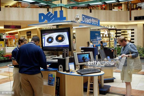 Dell computers sales representatives work with a customer at a Dell Direct Store kiosk in a shopping mall August 13, 2004 in Northbrook, Illinois....