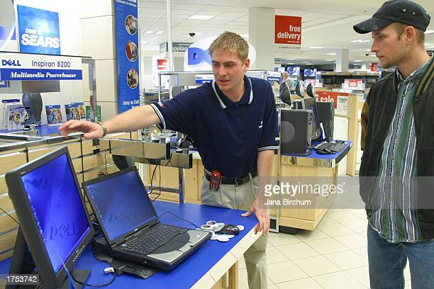 Dell employee Ryan McKnight shows customer Coy Clayton a new Dell computer system at a Sears Roebuck department store in Lakeline Mall January 30,...