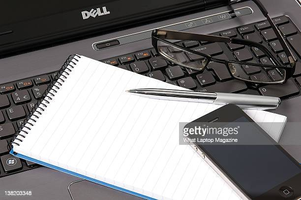 Dell laptop with an iPhone, notepad, pen and glasses, Bath, May 9, 2011.