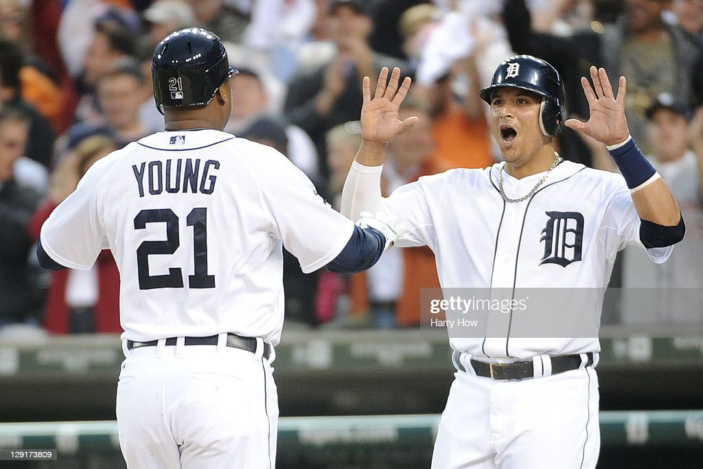 Delmon Young #21 and Victor Martinez #41 of the Detroit Tigers celebrate after Young's two-run home run in the sixth inning of Game Five of the American League Championship Series against the Texas Rangers at Comerica Park on October 13, 2011 in Detroit, Michigan.
