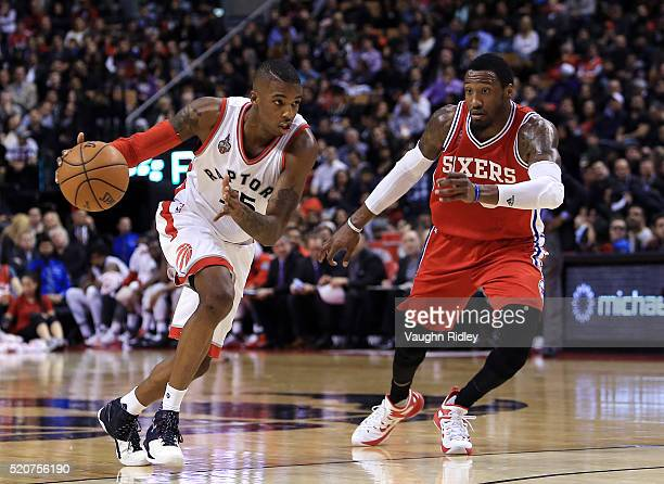 Delon Wright of the Toronto Raptors dribbles the ball as Robert Covington of the Philadelphia 76ers defends during the second half of an NBA game at...