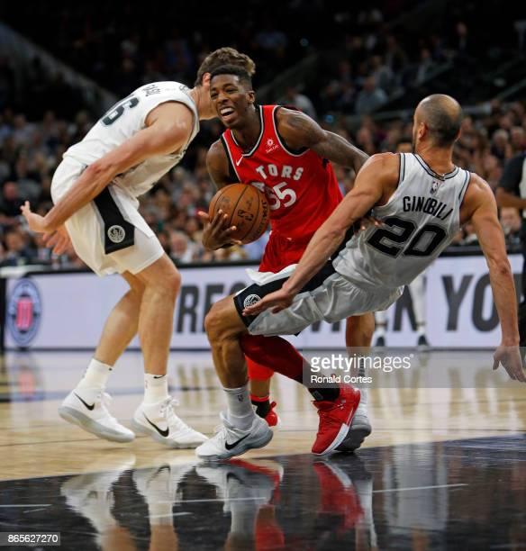 Delon Wright of the Toronto Raptors drives between Manu Ginobili and Pau Gasol of the San Antonio Spurs at ATT Center on October 23 2017 in San...