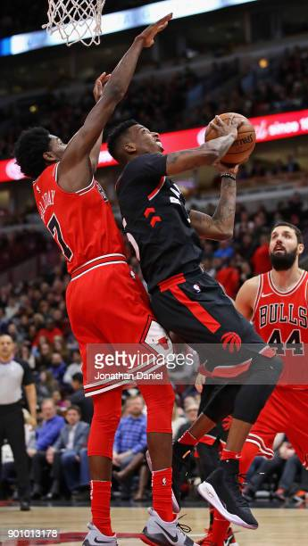 Delon Wright of the Toronto Raptors puts up a shot under pressure from Justin Holiday of the Chicago Bulls at the United Center on January 3 2018 in...