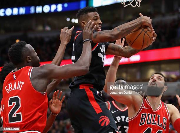 Delon Wright of the Toronto Raptors rebounds between Jerian Grant and Nikola Mirotic of the Chicago Bulls at the United Center on January 3 2018 in...