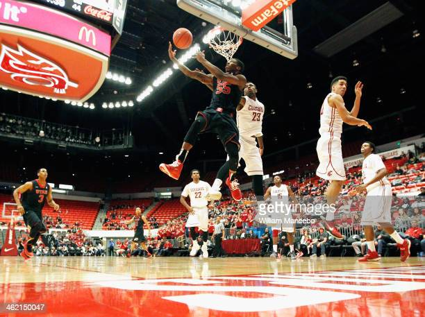 Delon Wright of the Utah Runnin' Utes goes in for a reverse layup against DJ Shelton of the Washington State Cougars during the second half of the...