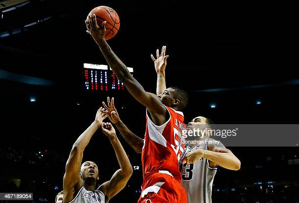Delon Wright of the Utah Utes goes up against Paul White and Mikael Hopkins of the Georgetown Hoyas in the first half during the third round of the...