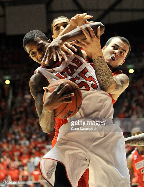 Delon Wright of the Utah Utes is guarded by Gabe York and TJ McConnell of the Arizona Wildcats in overtime at the Jon M Huntsman Center February 19...