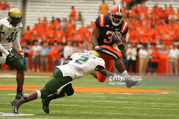 Delone Carter of the Syracuse Orange hurdles Quenton Washington of the South Florida Bulls during the game at the Carrier Dome on October 3, 2009 in...