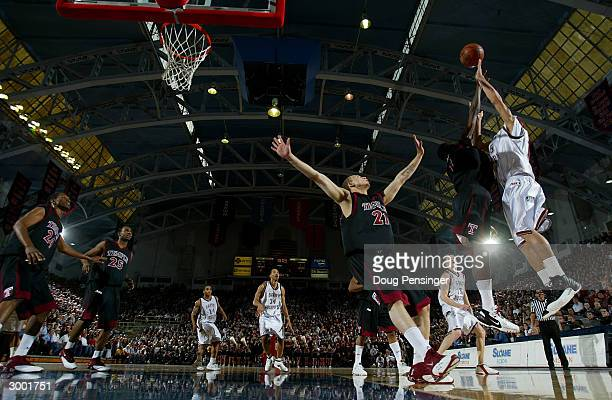 Delonte West of the Saint Joseph's University Hawks gets off a shot over Tyreek Byard and Michael Blackshear of the Temple University Owls as the...