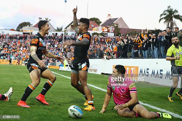 Delouise Hoeter of the Wests Tigers celebrates with Kevin Naiqama of the Wests Tigers after he scored a try during the round 16 NRL match between the...