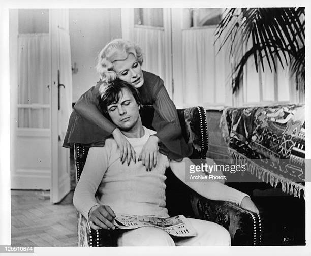 Delphine Seyrig hugs John Karlen who sits in chair in a scene from the film 'Daughters Of Darkness' 1971