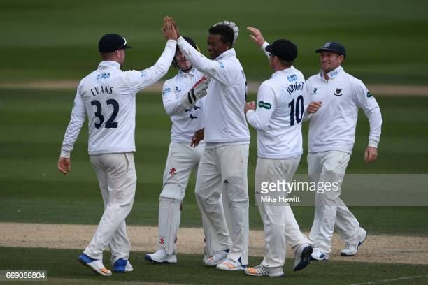 Delray Rawlins of Sussex is congratulated by team mateas after taking the wicket of Will Gidman during day three of the Specsavers County...